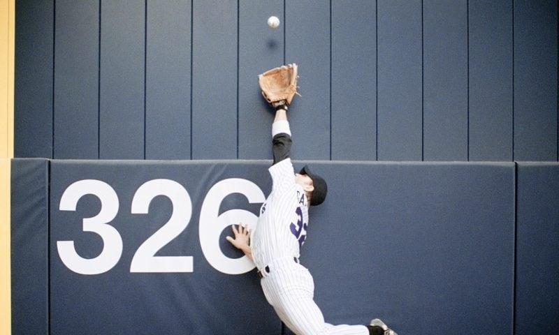 A baseball player catches a ball